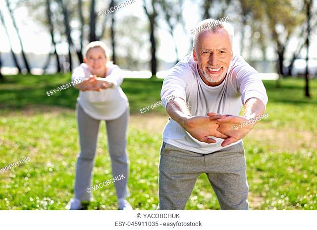 Useful exercise. Cheerful aged man leaning forward while doing exercises