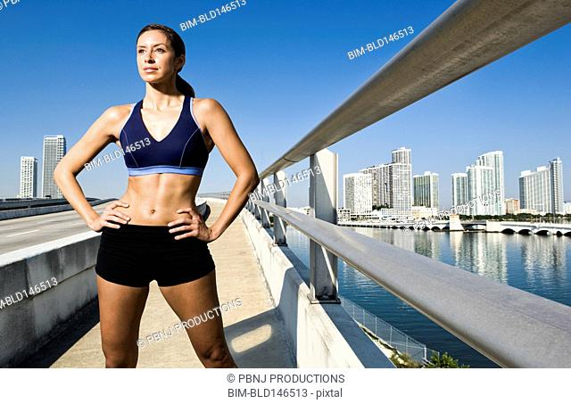 Hispanic woman in sportswear standing near urban waterfront