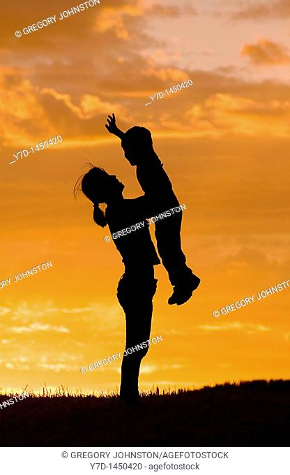 A mother holds her little sun up in the air during sunset