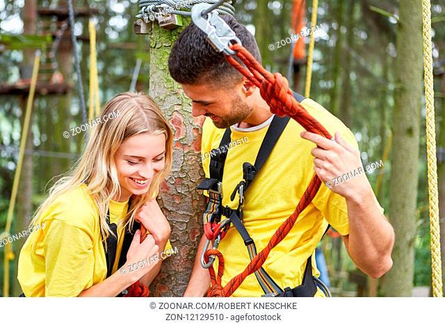 Junges Paar in einem Workshop für Teambuilding flirtet miteinander im Kletterwald
