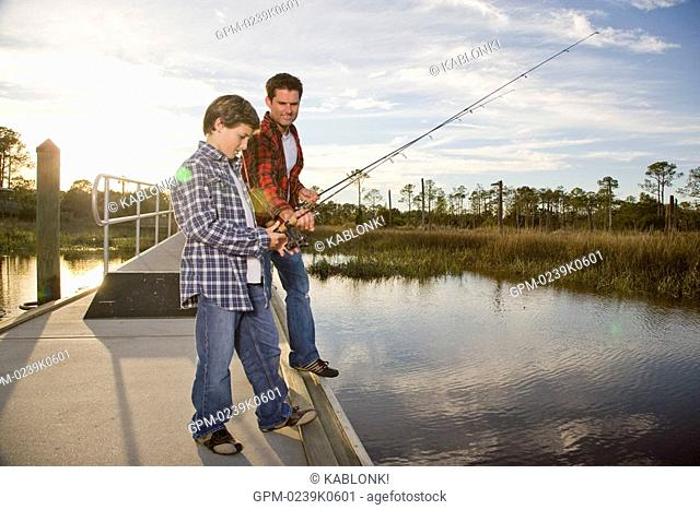 Happy son and father fishing by river, side view