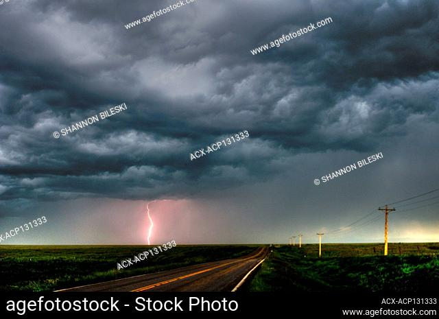 Storm with lightning flashing over highway in rural southern Manitoba Canada