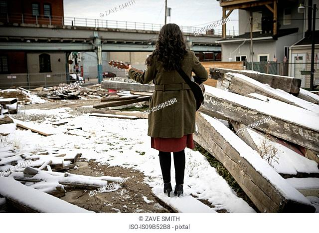 Rear view of young woman on snowy city wasteland playing guitar