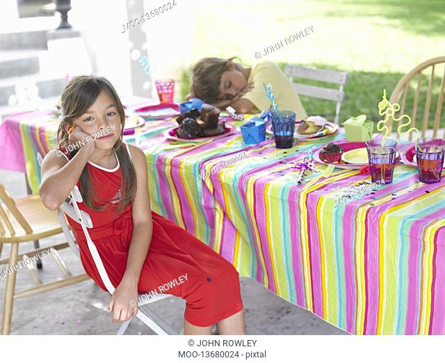 Girl and boy 7-9 at table after birthday party boy sleeping