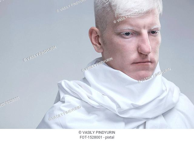 Close-up of thoughtful albino man against gray background