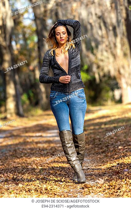 30 year old brunette woman down from the camera wearing a partially open sweater top walking on a path outdoors in the autumn
