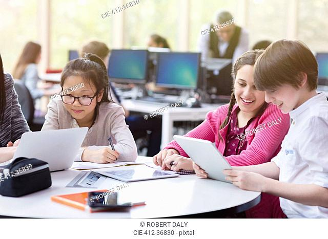 Students using digital tablet and laptop in library