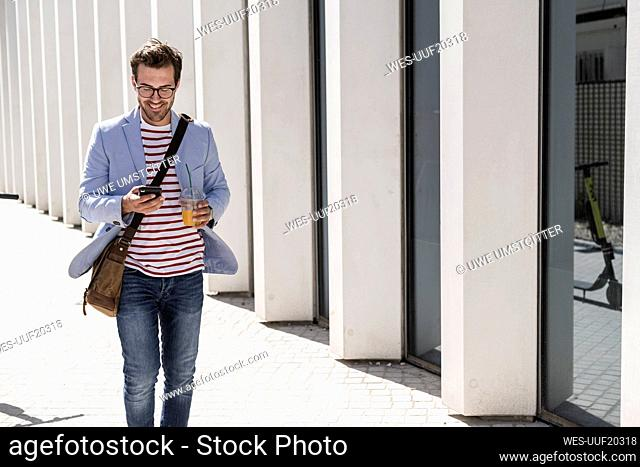 Young man walking in the city with cell phone and takeaway drink, Lisbon, Portugal