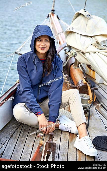 Young woman with raincoat, Sailing boat, Pasaia port, Gipuzkoa, Basque Country, Spain, Europe