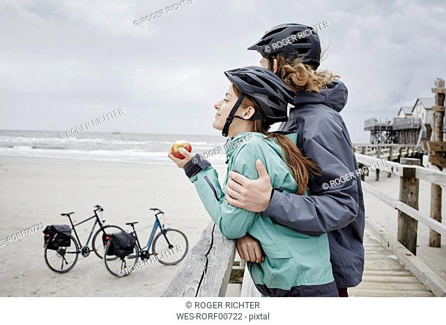 Germany, Schleswig-Holstein, St Peter-Ording, couple on a bicycle trip having a break on jetty at the beach