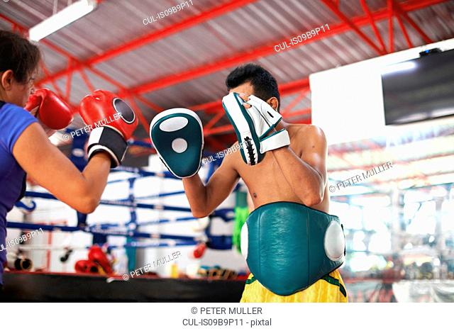 Mature woman practicing boxing with male trainer in gym