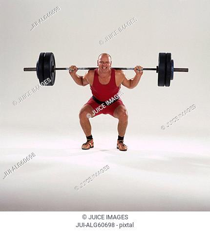 Bald-headed weightlifter lifting barbell