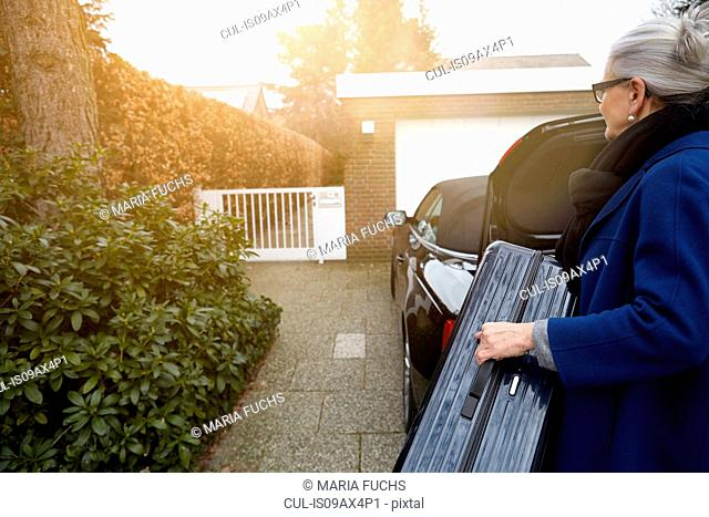 Woman on driveway in front of open car boot holding suitcase
