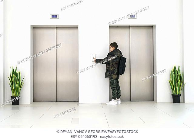 Boy with casual clothes and white sneakers call the elevator. White contemporary building interior. Flowers in pots and white wall
