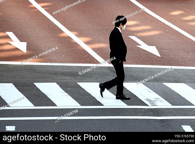 young Japanese male in black suit with mask on face walking across pedestrian crossing, Tokyo, Japan, Asia