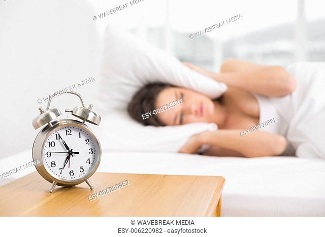 Woman covering ears with pillow in bed and alarm clock on table