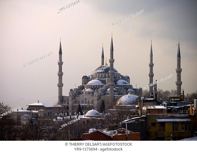 Shy sunrise in winter on the snowy Sultan Ahmed Mosque Turkish: Sultanahmet Camii also called blue mosque, Istanbul, Turkey, with the fogy Bosphorus in the back