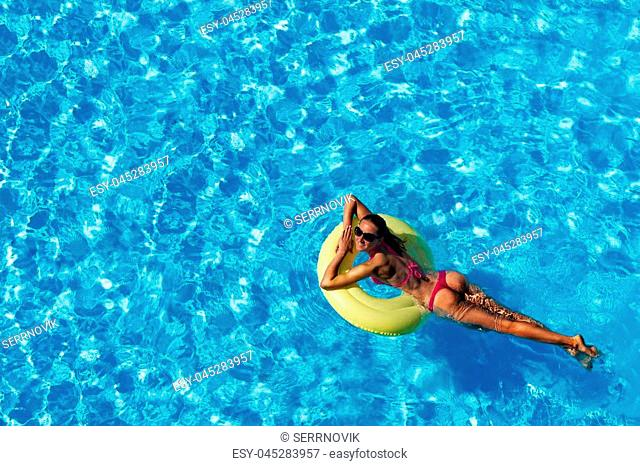 Smiling young woman in sunglasses and pink bikini swimming on yellow inflatable ring in the pool