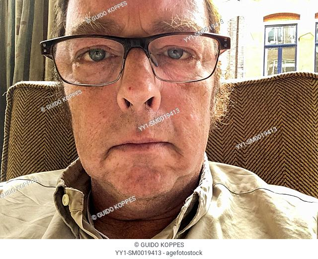 Tilburg, Netherlands. Selfie or self portrait of a caucasian senior adult man wearing glasses