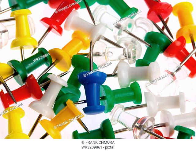Closeup of Many Colored Thumbtacks on White