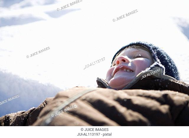 Close up of boy lying in snow