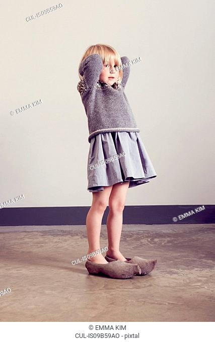 Girl standing in vintage wooden clogs with hands behind head