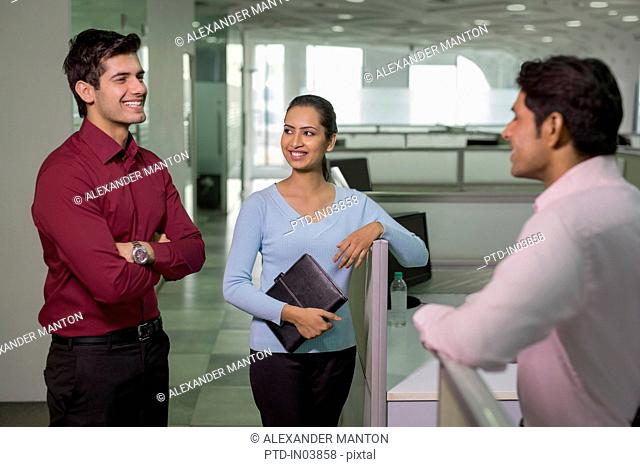 India, Colleagues standing in office and talking