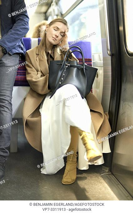 exhausted fashionable blogger woman sitting in metro, using public transportation, during fashion week, in city Paris, France