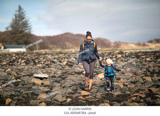 Mother and son holding hands walking on rocks