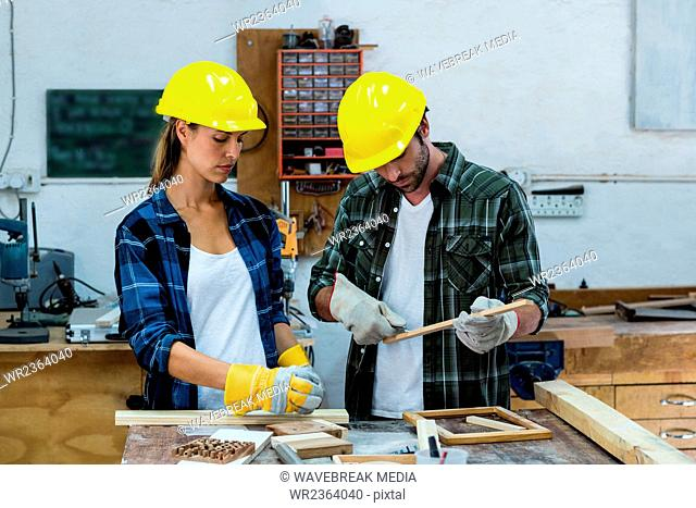 Male and female carpenters marking on wooden plank with pencil