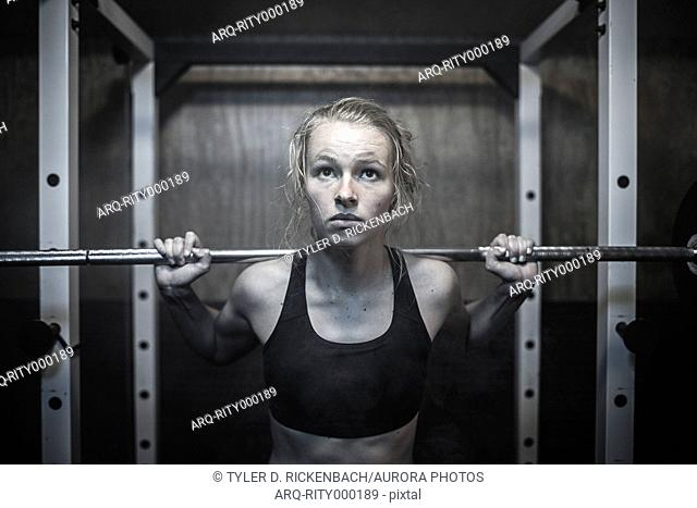 A young female athlete does a squatting exercise in a grungy home gym