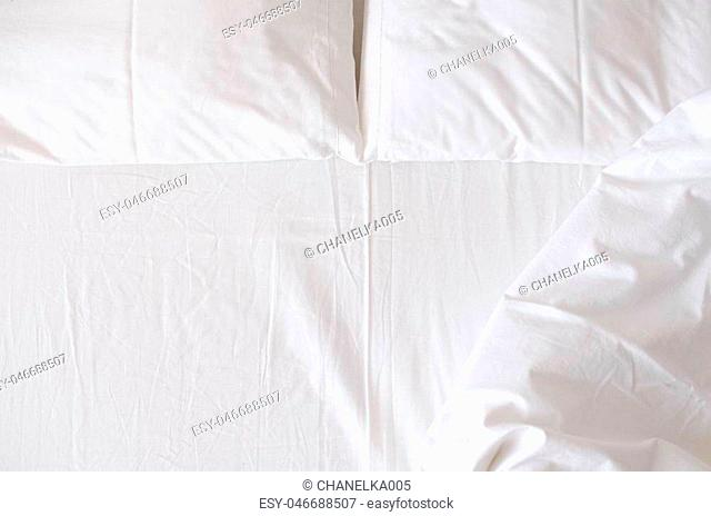 White bedding sheet, blanket and pillows in the hotel room. Rest, sleeping, comfort concept. Top view. Copy space