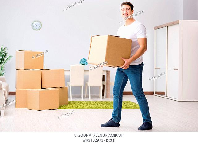 Young man moving boxes at home