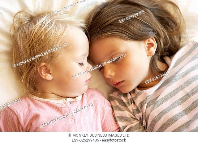 Two Young Girls Sleeping In Bed