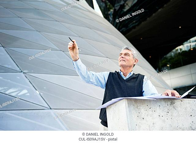 Senior adult businessman looking up, holding pen and plans