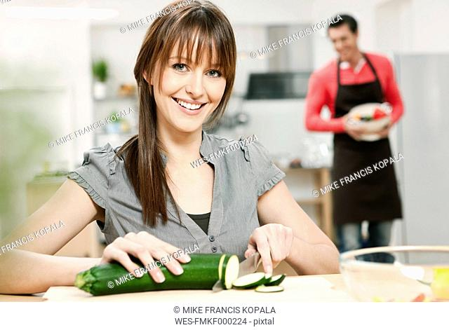 Germany, Cologne, Woman chopping cucumber in kitchen