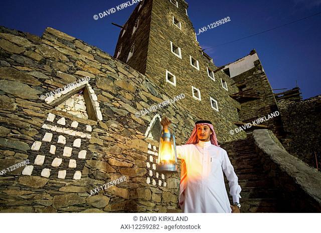 Man with lamp outsude Rijal Alma village; Asir Province, Saudi Arabia