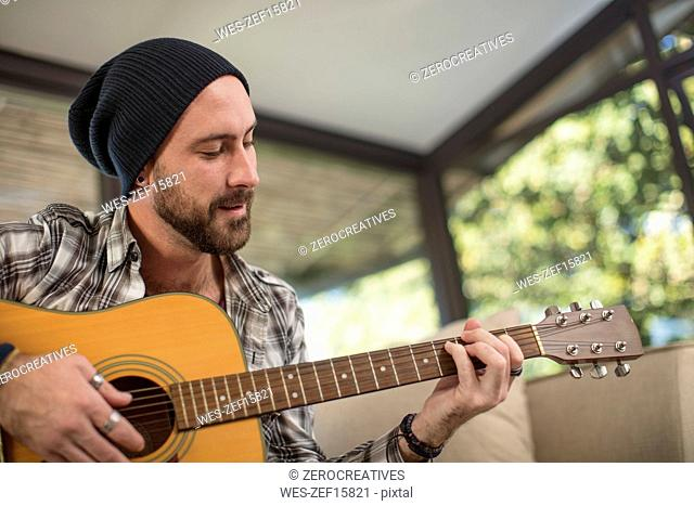 Young man at home sitting on couch playing guitar