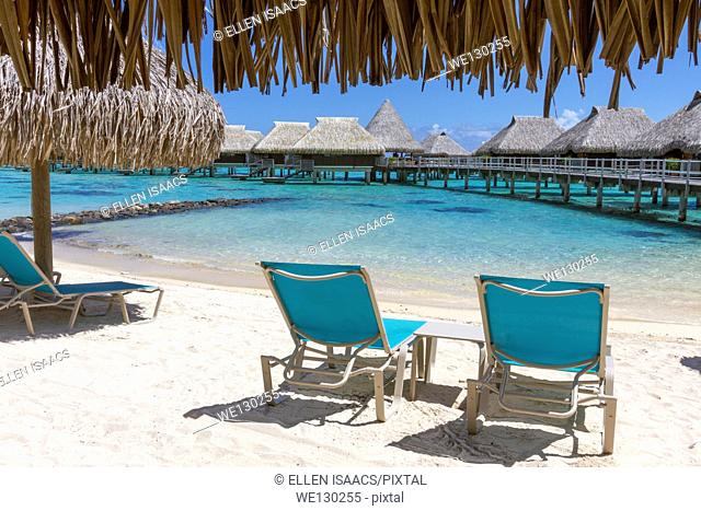 Lounge chairs on beach by thatched roof hut overlooking overwater bungalows in French Polynesia