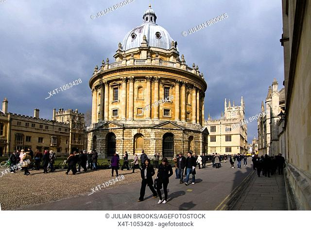 A group of tourists walking past the Radcliffe camera, Oxford  in the sunshine with clouds gathering behind