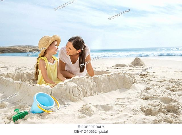 Mother and daughter making sandcastle on beach