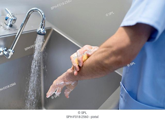 Doctor cleaning hands with soap and water in hospital