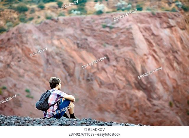 Young tourist man with backpack sitting on rocky cliff and enjoying beautiful view