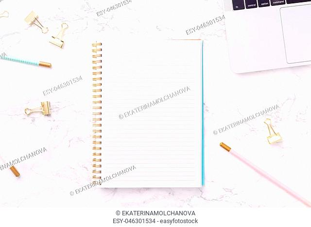 Festive golden stationary on white marble background. Feminine job, gender equality, home office and career concept. Copy space Top view. Horizontal