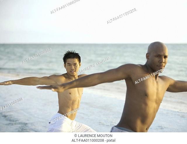 Two men doing relaxation exercise on beach