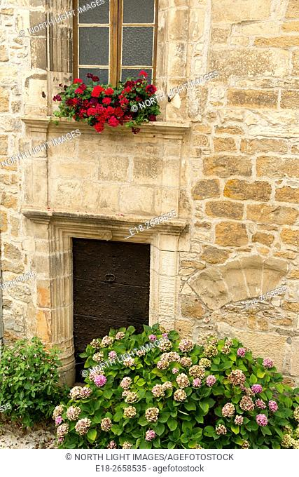 France, Midi-Pyrénées, Carrenac. Flower filled window box, and flowering hydrangea adorn the front of a home in this quaint Dordogne valley village