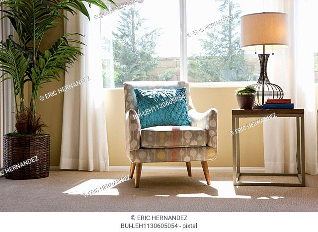 Blue throw pillow on arm chair by window