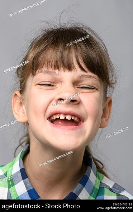 Portrait of a joyfully smiling ten-year-old girl of European appearance, close-up