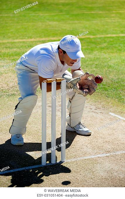 Wicketkeeper catching ball behind stumps on field