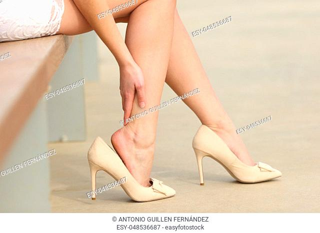 Close up of a woman wearing high heels touching painful legs in the street